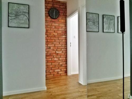 ruda chata-blog-funkcjonalny przedpokoj-ergonomia w mieszkaniu-cegla-zegar-plakat-podloga drewnopodobna-lustro-biala sciana