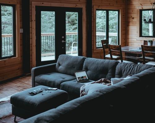 ruda chata-blog-jak ustawić kanapę w salonie-narożnik-szary-drewniany domek-stół z krzesłami-laptop-las za oknem