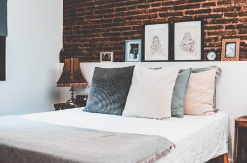 ruda chata-blog-funkcjonalna sypialnia-ergonomia w mieszkaniu-cegła w sypialni-poduszki-duże łóżko-plakaty