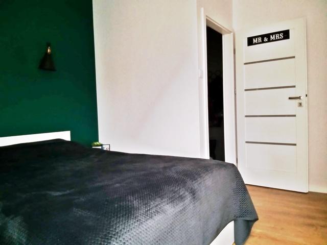 ruda chata-blog-sypialnia zzieloną scianą-butelkowa zieleń-białe łóżko-jasna sypialnia-białe drzwi