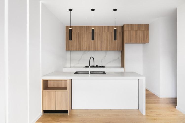 janiszewska marta-suwałki-jak przygotowac mieszkanie na wynajem-home staging-drewniano biała kuchnia-wyspa w kuchni-nowoczesne lampy